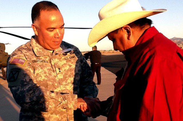 Maj. Gen. Anthony G. Crutchfield, USAACE and Fort Rucker commanding general, gives a coin to one of the Apache Council members involved in the blessing of the first Apache Block III Longbow Nov. 2 in Mesa, Ariz.