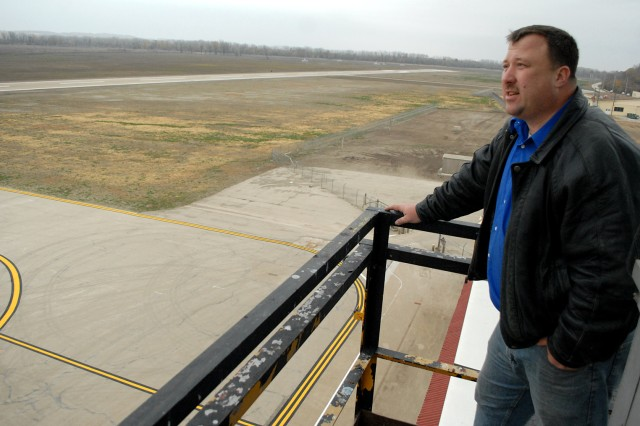 Air Traffic Assistant Billy Summers looks out over the airfield at the newly painted runway and decimated grass Nov. 7, 2011, at Sherman Army Airfield, Fort Leavenworth, Kan. SAAF reopened to limited operations, daylight hours only as runway lights must be replaced, after being closed since June when three to seven feet of floodwater filled the area.