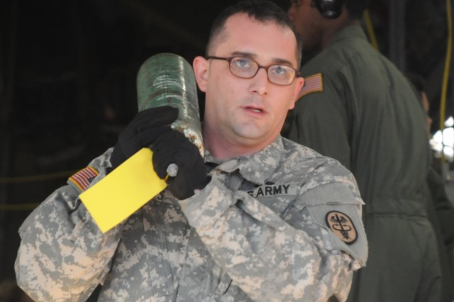 Army Spc. Bryon Otts carries an oxygen tank from a recently landed C-17 Globemaster to a waiting Walter Reed National Military Medical Center (WRNMMC) patient evacuation vehicle Nov. 04, 2011 on the flight line at Joint Base Andrews, Md. Otts has been assigned at WRNMMC for the past year and a half.