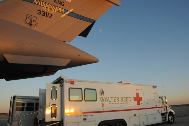 A familiar sight.  An Air Force C-17 Globemaster's tail end opens towards the open doors of a waiting Walter Reed National Military Medical Center (WRNMMC) patient evacuation vehicle on the flight line at Joint Base Andrews, Md., Nov. 04, 2011.
