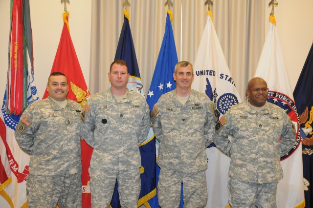 U.S. Army Military District of Washington Medical Evacuation to CONUS Hospitals (MDW MECH) Soldiers Master Sgt. Juan D. Reyna, Team Deputy Chief, Sgt. 1st Class Tommy Bish, Team NCOIC, Col. Claude Schmid, Team Leader and Sgt. 1st Class Patrick Marcel, Team NCOIC pose for a picture at their home station on Fort McNair, D.C.