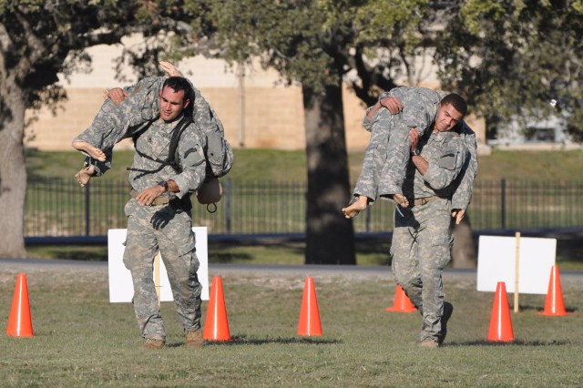 Soldiers carry an 180-pound simulated casualty during the physical fitness challenge event Nov. 4, 2011, at Camp Bullis, Texas.
