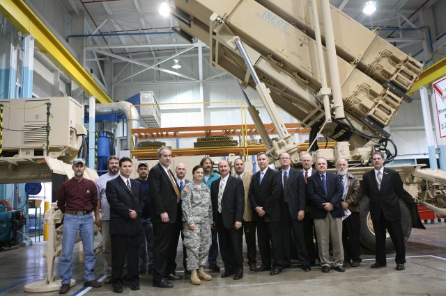 Letterkenny Army Depot Commander, Col. Cheri A. Provancha and Mr. Scott Jackson, PATRIOT program manager, along with Raytheon and Lower Tier Project Office representatives pause for a photo in front of the PATRIOT PAC-3 launcher station with the Letterkenny employees charged with the PATRIOT Launcher New Build mission.
