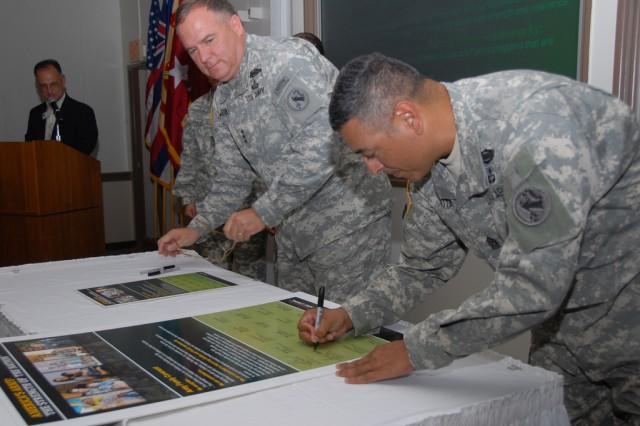 The USARPAC command team of Lt. Gen. Francis Wiercinski (left), commander; and Command Sgt. Maj. Frank Leota, senior enlisted leader, sign the AFC at Schofield Barracks, Oct. 20.