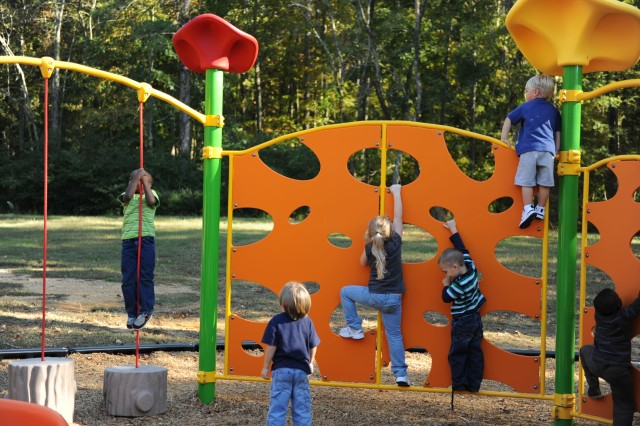 Students in the Anniston Army Depot Child Development Center's pre-kindergarten class climb a wall at the depot's newest playground. This Americans with Disabilities Act-compliant equipment has several interactive boards with sounds run completely on kid power.