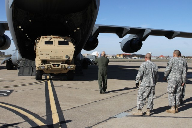 "Members of the Singapore Armed Forces observe as U.S. Soldiers from 1st Battalion, 14th Field Artillery at Fort Sill, Okla., load an M142 High Mobility Artillery Rocket Launcher onto a C-17 aircraft as part of ""Daring Warrior,"" a combined exercise."
