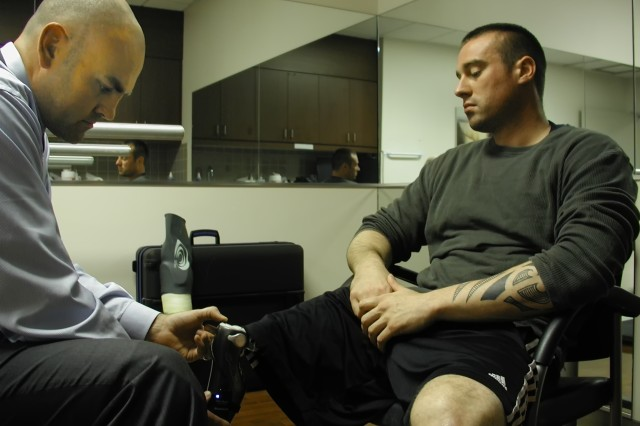 Orthotist Scott Gray adjusts the prosthetic leg of Tristan Wyatt during a fitting at the VA San Diego Healthcare System. Wyatt, who is now assistant chief of prosthetics at VASDHS, has overcome his injuries with the help of prosthetics and helps other veterans do the same.