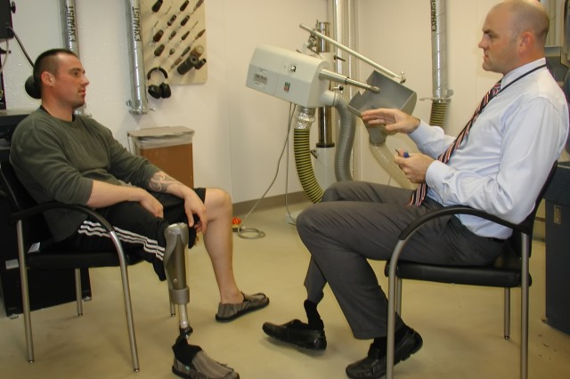 Prosthetic department colleagues Scott Gray and Tristan Wyatt converse at the San Diego VA Medical Center's prosthetic limb machinery shop. Wyatt, who is assistant chief of prosthetics at the VA San Diego Healthcare System, is helping other veterans recover from traumatic injuries.