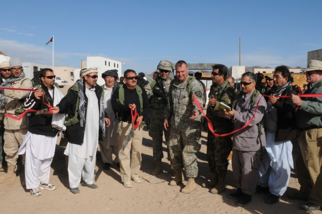 Col. Barry F. Huggins, commander 2nd Brigade, 2nd Infantry Division (Center) cuts the ceremonial ribbon in the fictional town of Sorkh Kotal Mezre, Nov. 12, National Training Center, Fort Irwin, Calif.  Col. Huggins was in the town attending the opening of the Sorkh Kotal Mezre Pass.