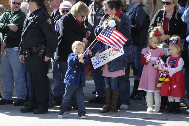 A little boy vigorously waves the American flag during the Veterans Day parade in Knoxville, TN.