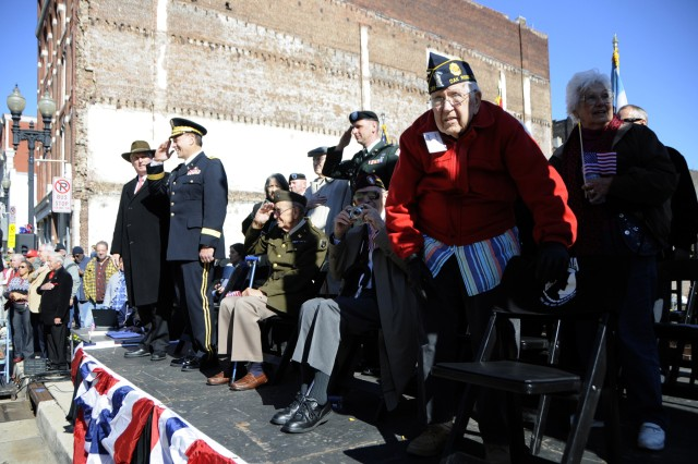 Maj. Gen. Gill Beck, commander of the 81st Regional Support Command, returns salutes at the Veterans Day parade in Knoxville, TN. To Beck's left is WWII veteran 2nd Lt. Robert Bailey, seated and saluting, Master Sgt. Heffron. Standing in the red jacket is former WWII POW John W. Clark, who was held prisoner in Japan in Nagasaki until the atomic bomb was dropped there. On the far right is Mrs. Vernice Bailey, 2nd Lt. Bailey's wife of 69 years