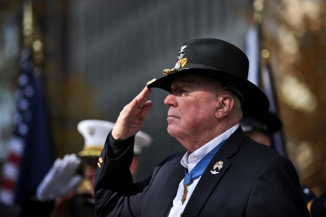Retired Army Col. Bruce P. Crandall, recipient of the Medal of Honor, salutes during the playing of the National Anthem at Madison Square Park in New York City, N.Y., during Veterans Day activities honoring war veterans Nov. 11, 2011.