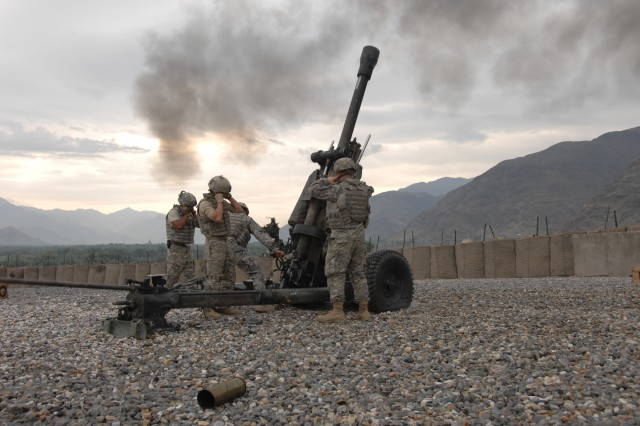 Soldiers fire an M119 Howitzer.