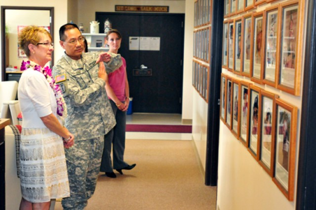 """Anita Dixon (left) and Col. Colbert Low, commander, 4960th Multifunction Training Bde., 9th MSC, view her son's, Sgt. Evan Parkers, image placed on the """"Wall of Remembrance"""" at Survivor Outreach Services, Fort Shafter, Oct. 26."""