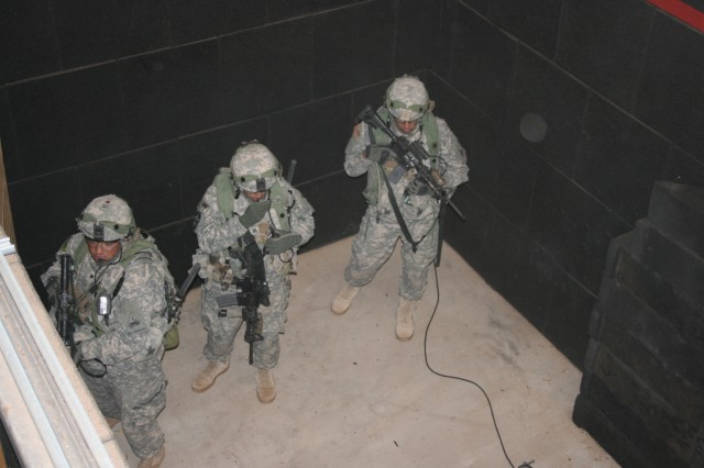 Soldiers from 1st Battalion, 35th Infantry Regiment, 2nd Brigade Combat Team, 1st Armored Division, engage in a simulated raid using wearable computer system and held hand devices during the Network Integration Evaluation 12.1 exercise at White Sands Missile Range, N.M.