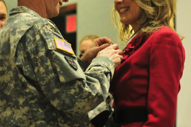 """FORT CARSON, Colo. """" Lieutenant General Howard B. Bromberg, deputy commanding general and chief of staff, U.S. Army Forces Command, presents Ginger Perkins with the Department of the Army Outstanding Civilian Service medal in appreciation for her work during her time with the 4th Infantry Division Family Readiness Group, Nov. 16, 2011. While her husband Maj. Gen. David G. Perkins, served as the commanding general of 4th Inf. Div. and Fort Carson, Ginger committed personal time and effort to meeting the needs of Fort Carson Families."""