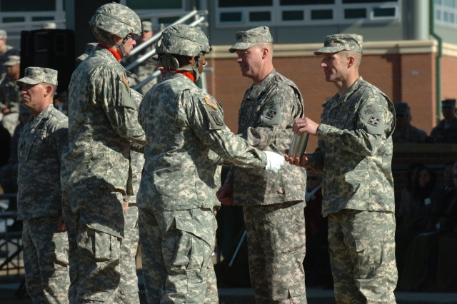 """FORT CARSON, Colo. """" From left, 2nd Lieutenant Lucas Waniewski, a fire direction officer, and Staff Sgt. Charles Paris, Jr., Paladin section chief, both assigned to Battery B, 3rd Battalion, 29th Field Artillery Regiment, 3rd Brigade Combat Team, 4th Infantry Division, present Maj. Gen. David G. Perkins and Command Sgt. Maj. Daniel A. Dailey, with the shells of the last rounds fired in their honor during a change of command ceremony at Fort Carson, Nov. 16, 2011. Perkins and Dailey said farewell to the 4th Inf. Div. and the """"Mountain Post"""" during the ceremony held at Manhart Field. Maj. Gen. Joseph Anderson assumed command of the """"Ivy"""" Division and Fort Carson during the ceremony."""