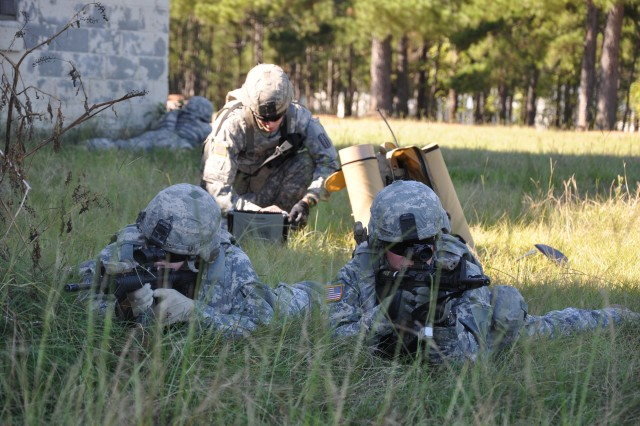 """Sgt. Justin Rasmussen, A Company, 1st Battalion, 29th Infantry Regiment, and Sgt. Robert Richmond from Fort Bliss, Texas, pull security while Spc. Corey Battaglia, also from A Company, 1-29 Inf. """" the experimentation force, or EXFOR """" sets up the Night Hawk computer system at the McKenna MOUT Site Oct. 5 during AEWE training. The Night Hawk is an unmanned aircraft system being used in the experiments during Spiral G of the Army Expeditionary Warrior Experiment."""