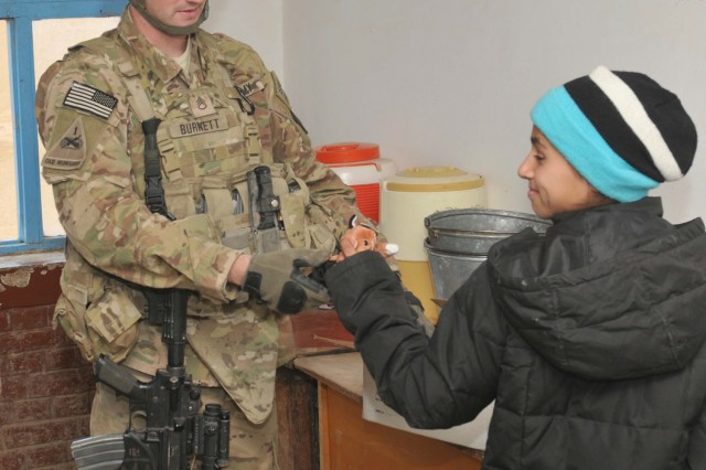 """Staff Sgt. Sean Burnett, now a squad leader with Headquarters and Headquarters Company, 40th Engineer Battalion, 170th Infantry Brigade Combat Team, hands a stuffed animal to a student Balkh Province, Afghanistan, Nov. 15, 2011. Soldiers with """"Havoc"""" Company patrolled to three schools and distributed roughly 100 pounds of scholastic and hygienic supplies."""