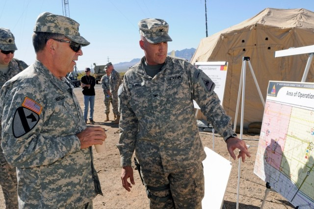 Vice Chief of Staff of the Army Gen. Peter W. Chiarelli is briefed by Col. Daniel Pinell, 2nd Brigade Combat Team, 1st Armored Division commander, during a visit to White Sands Missile Range, N.M., Nov. 15, 2011. The visit was part of the Network Integration Evaluation where new Army communication technologies are being tested during a series of simulated missions.