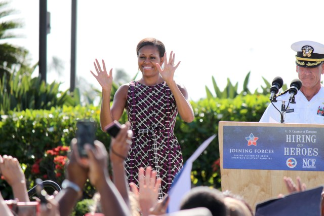 "First lady Michelle Obama arrived at Joint Base Pearl Harbor-Hickam, Monday, for her ""Hiring our Heroes"" speaking engagement, bearing a smile and waving to the cheering crowd of service members from all branches, veterans and military families. Escorting her was Capt. Jeffrey James (at podium), commander, JBPHH; and Kevin Schmiegel, vice president, Veterans Employment Program, U.S. Chamber of Commerce."