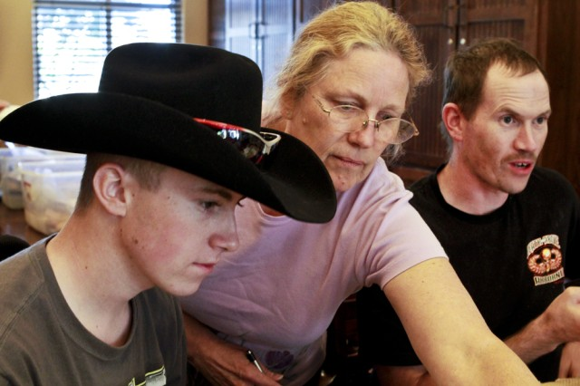 Saralee Trimble offers suggestions to her son, Pfc. Kevin Trimble (left), as he works on a leather project with his brother, Ben, at the Warrior and Family Support Center in San Antonio, Nov. 10, 2011.