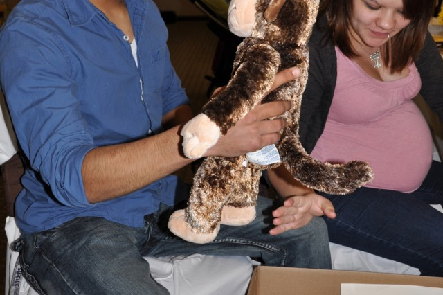 Private 1st Class Joseph Arsola, a cargo specialist with the 372nd Transportation Company, 129th Combat Sustainment Support Battalion, 101st Sustainment Brigade, 101st Airborne Division, smiles as he looks at a monkey his wife Victoria handed him as they begin looking through a box of items for their baby during Operation Shower, Saturday. The first-time parents, who were only five days away from the expected due date for their son, were excited to be among more than 50 moms-to-be, and a few dads who came with their wives, who received new donated items inlcuding clothes, toys, humidifiers and cribs. A majority of the moms-to-be are spouses of deployed Soldiers, some are Soldiers and others are wives of injured service members. (Photo by Nondice Thurman, Fort Campbell Courier staff.)