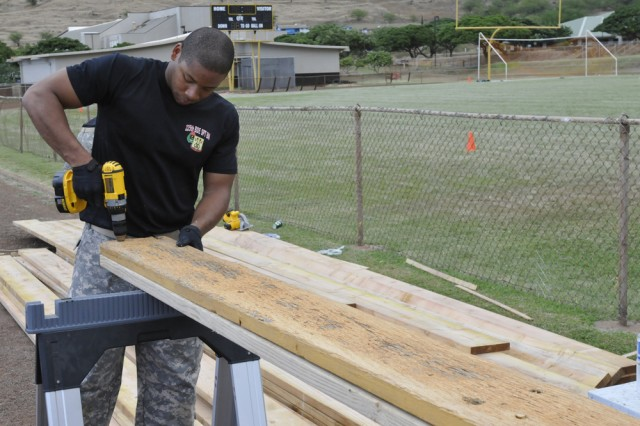 WAIANAE, Hawaii -- Sgt. Charlie Alston Jr. of 225th Brigade Support Battalion, 25th Infantry Division prepares new lumber to replaced damaged seats on the bleachers at the Nanakuli High and Intermediate School as part of the Partnership of Ohana Nov. 10 here. The work at the school will raise seating capacity at the athletic field to approximately 5,000 up from 3,500.