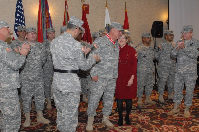 Command Sgt. Maj. Guy Taylor embraces his wife Sheryl after receiving the Bronze Order of the De Fleury medal for inspirational leadership to the U.S. Army Corps of Engineers during his retirement ceremony in Nashville, Tenn., Nov. 19, 2011.