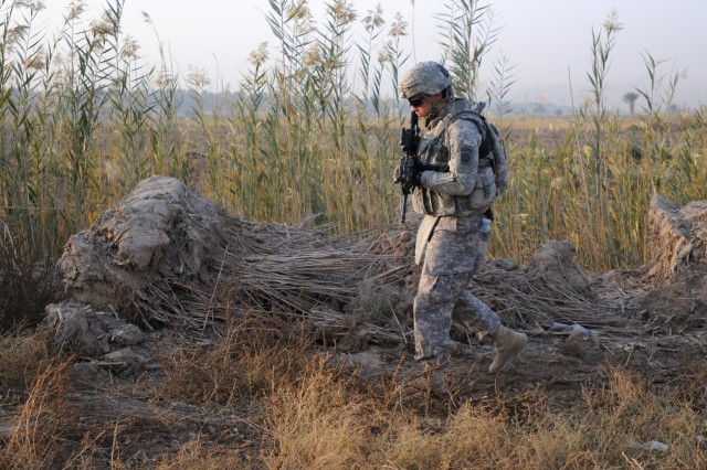 "BAGHDAD, Iraq "" Pvt. Jordan Heistand, a rifleman assigned to the 2nd Brigade, 82nd Airborne Division's A Troop, 1st Squadron, 73rd Cavalry Regiment, walks past piles of brush and tall weeds while searching the area for roadside bombs on Nov. 15. Paratroopers from A Troop secured a route in Baghdad for other units from the brigade traveling from Camp Ramadi to Kuwait. The troop made several stops along the route to check the area on foot for improvised explosive devices and meet with Iraqi Army soldiers at IA checkpoints. The 2nd Brigade is the last brigade in Baghdad and is facilitating the withdrawal of U.S. military forces from Iraq. Heistand is a native of Portland, Ore."