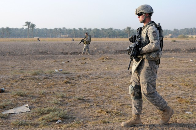 Pvt. Zachary Vanlerberg, a cavalry scout, and Paratroopers assigned to the 2nd Brigade, 82nd Airborne Division's A Troop, 1st Squadron, 73rd Cavalry Regiment, walks through a field parallel to a main convoy route on Nov. 15, searching the area for roadside bombs on Nov. 15. Paratroopers from A Troop secured the route in Baghdad for other units from the brigade traveling from Camp Ramadi to Kuwait. The troop made several stops along the route to check the area on foot for improvised explosive devices and meet with Iraqi Army soldiers at IA checkpoints. The 2nd Brigade is the last brigade in Baghdad and is facilitating the withdrawal of U.S. military forces from Iraq. Vanlerberg is a native of Pittsford, Mich.