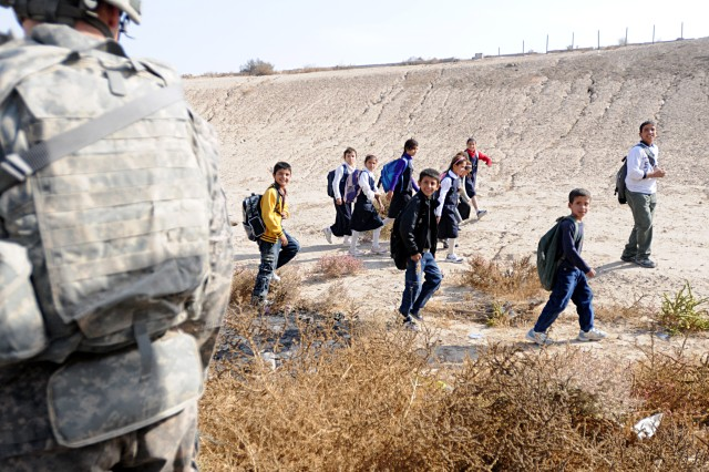 Iraqi children walking to school smile as they pass closely by Paratroopers assigned to the 2nd Brigade, 82nd Airborne Division's A Troop, 1st Squadron, 73rd Cavalry Regiment, pulling security on a main convoy route in Baghdad. The Paratroopers pulled security for other units from the brigade traveling from Camp Ramadi to Kuwait. The troop made several stops along the route to check the area on foot for improvised explosive devices and meet with Iraqi Army soldiers at IA checkpoints. The 2nd Brigade is the last brigade in Baghdad and is facilitating the withdrawal of U.S. military forces from Iraq.