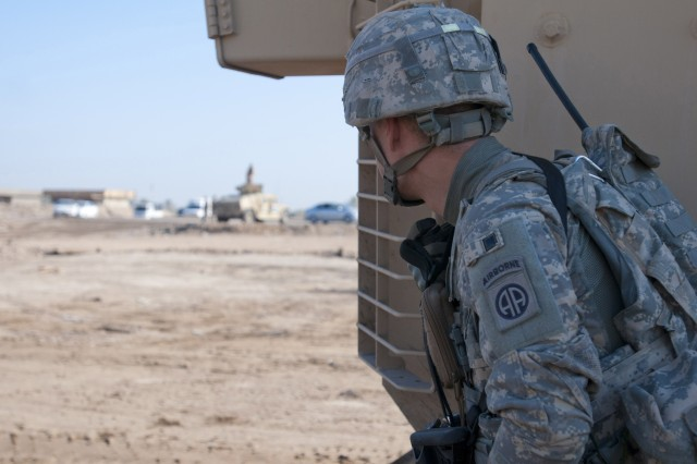 Sgt. Eric Janson, an infantryman assigned to D Co., 2nd Battalion, 325th Airborne Infantry Regiment, 2nd Brigade, 82nd Airborne Division, peers around from the cover of his armored vehicle toward a highway in Baghdad after hearing gunfire in the distance, Nov. 18. Paratroopers with D Co. are responsible for securing the route for convoys traveling south to Kuwait. The 2nd Brigade is the last brigade in Baghdad and continues to partner with Iraqi Security Forces to facilitate the withdrawal of U.S. military forces from Iraq. Janson is a native of Fayetteville, N.C.