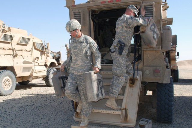 Soldiers arriving at Camp Virginia, Kuwait, remove fuel containers and communication equipment prior to turning in tactical vehicles.