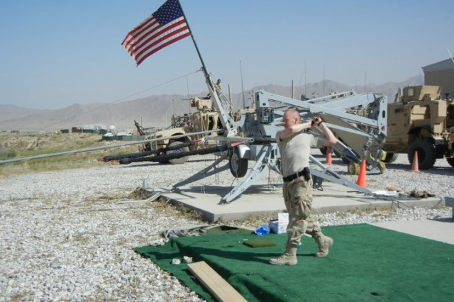BAGRAM AIR BASE, AFGHANISTAN - Travis Rodenburg practices his golf swing on a makeshift driving range in Afghanistan.