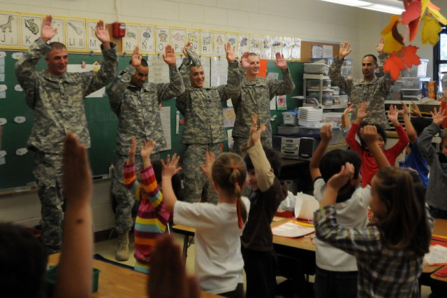 U.S. Army Spc. Jason Rogers, U.S. Army Pvt. Javier Moreno, U.S. Army Spc. Andrew Surber, U.S. Army Pfc. James Rowe and U.S. Army Staff Sgt. Juan Valdez participate in a cheer with a kindergarten class Nov. 16 at Polk Elementary School in El Paso. The Soldiers were there with the Fort Bliss Partnerships in Education Program.