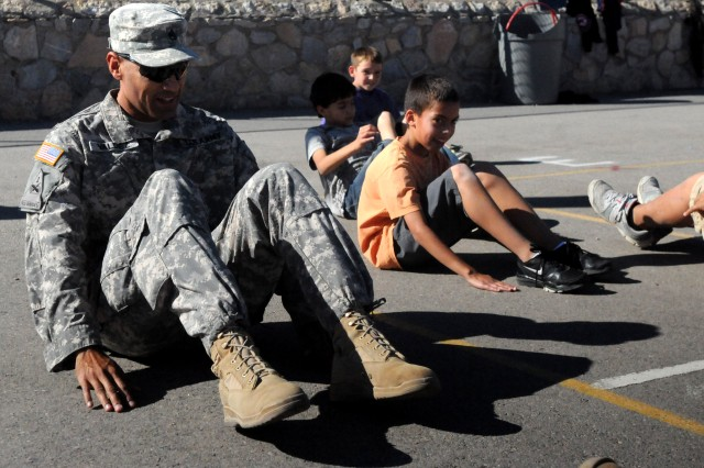 U.S. Army Staff Sgt. Juan Valdez does sit-ups during P.E. class with students Nov. 16 at Polk Elementary School in El Paso. Valdez was there with the Fort Bliss Partnerships in Education Program.