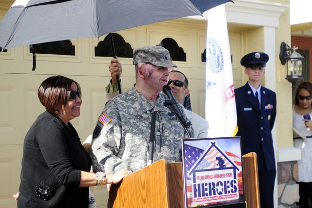 Sgt. Joel Tavera speaks to a crowd of family, friends, service members and volunteers alongside his mother and father, Maritza and Jose, during his homecoming ceremony, Nov. 19, 2011.