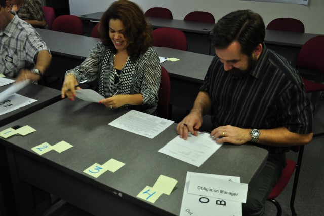 FORT BRAGG, N.C. (Nov. 16, 2011) -- Ellen Diaz-O'Neill, U.S. Army Forces Command (FORSCOM) G4 logistics management specialist, and Andy Almueti, FORSCOM Internal Review program management analyst, act as business obligation managers in a simulation to test process improvements during the Army Lean Six Sigma Green Belt Course conducted here, Nov. 14 - 18, 2011.  U.S. Army photo by Bob Harrison, FORSCOM Public Affairs.
