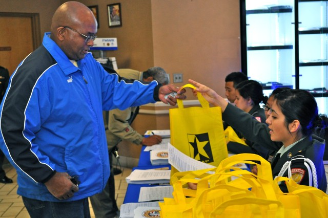 A retiree finishes registering into the event and receives a bag to fit all of the informational brochures and items that he may receive throughout the day Nov 19.