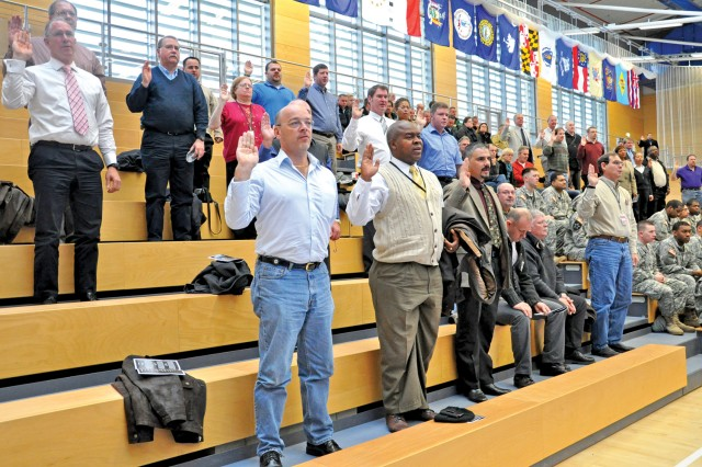 Civilian employees of the 5th Signal Command recite the oath of office during a special Operation Solemn Promise reaffirming ceremony at the Wiesbaden Fitness Center Nov. 17.