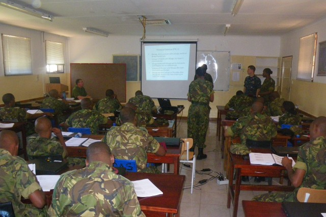Officers of the Botswana Tactical Intelligence Course cover an analytical tools lesson taught by Botswana Defense Force instructors. Randy Bretzin (far left), Regional Joint Intelligence Training Facility instructor and U.S. Navy Lt. Daniel Schumacher (right), from J24 U.S. Africa Command, sit back to evaluate the instruction.