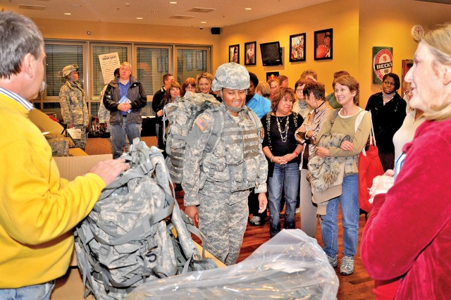 Pfc. Jennifer Rogers of the U.S. Army Garrison Wiesbaden models military protective gear and other items during the teachers orientation Nov. 8.