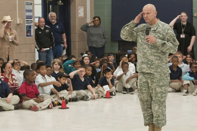 Chaplain (Lt. Col.) David Vanderjagt, the command chaplain for the 3d Sustainment Command (Expeditionary), teaches students the correct way to render a salute during his visit to Roosevelt Perry Elementary in Louisville, Ky. on Nov. 18.  During his visit, Vanderjagt spoke to students about the importance of the importance of care packages and supporting troops stationed in overseas combat zones. (U.S. Army photo by Staff Sgt. Michael Behlin)