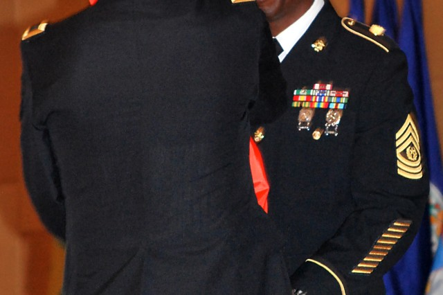 Command Sgt. Maj. Kennis J. Dent accepts the U.S. Army Communications-Electronics Command color during an assumption of responsibility ceremony Nov. 22, 2011, at the C4ISR Center of Excellence at Aberdeen Proving Ground.
