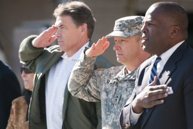 Texas Gov. Rick Perry and Maj. Gen. Robert E. Livingston Jr., adjutant general of South Carolina, and City of Columbia Mayor Steve Benjamin render honors during the singing of the national anthem at the opening ceremony of the Columbia, S.C., Veterans Day parade on Nov. 11.