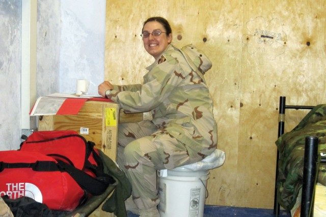 While on a site visit to FOB Lagman in Zabul province, Heather Moncrief used an ammunition-box desk and a five-gallon bucket chair as the work station in her bedroom. (USACE Photo/Michael Bell)