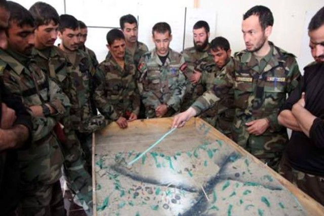 Members of the 1st Commando Kandak discuss objectives on a sand table during a mission brief for an upcoming clearing operation in Merdesh village, Kamdesh district, Nov. 17.  The operation was successful in disrupting insurgent freedom of movement and resulted in 21 insurgents killed and seven detained by the Commandos.