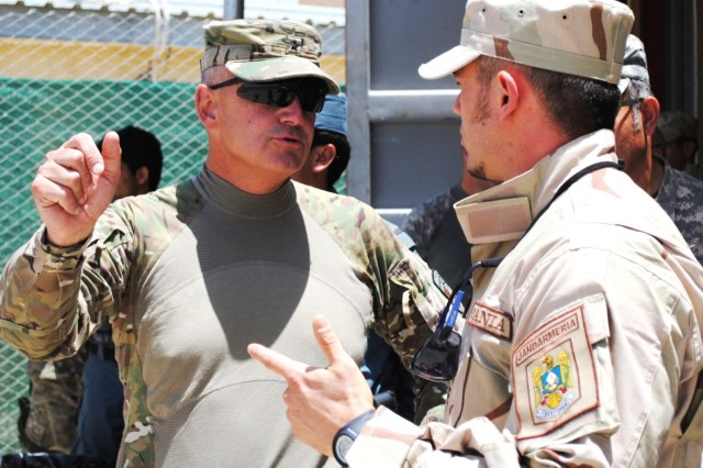 Brig. Gen. Tom Cosentino discusses training with a member of the Romanian Gendarmerie contingent at Spin Boldak June 16, Kandahar province. The Romanian Gendarmerie began advising Afghan National Police trainers in April. (Photo by Air Force Tech Sgt. Adrienne Brammer)