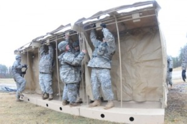 Members of the 16th Quartermaster Company put the finishing touches on a portable shower unit.  A large tent will cover the structure.  Sinks may also be installed within the facility.